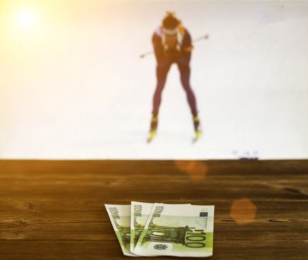 Euro money on the background of the TV on which the biathlon show, sports betting, euro Banco de Imagens