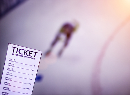 Bookmaker ticket on the background of a TV on which show skating sports, sports betting, skating