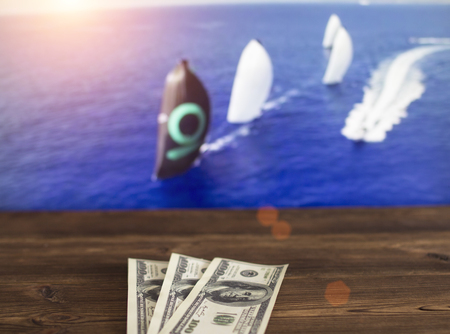 Money dollars on the background of a TV on which show sailing, sports betting, yachting sport