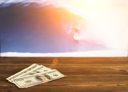 Money dollars on the background of a TV on which show surfing, sports betting, surfing