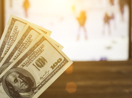 Money dollars on the background of a TV on which the biathlon show, sports betting, dollars
