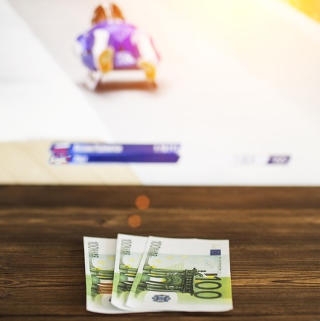 Euro money on the background of the TV on which show toboggan, bobsled, sports betting, toboggan Standard-Bild - 110687460