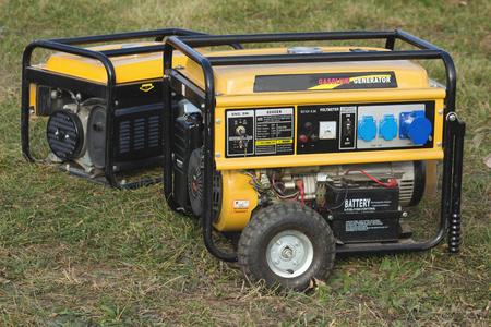 gelber tragbarer Benzingenerator auf Rädern, Nahaufnahme, Notfall Standard-Bild