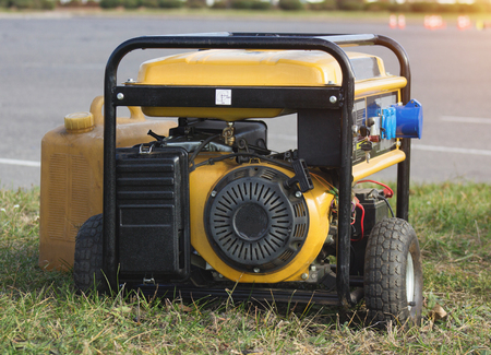 yellow petrol portable generator on wheels, close-up, alternator