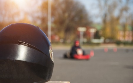 Karting competitions, black racing helmet against the background of karting competitions, championship