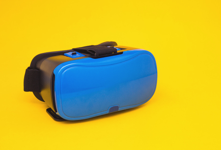 Modern blue glasses of virtual reality for smartphone and phone on yellow background, close-up, multimedia, simulator Stock Photo