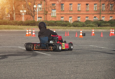 Go-kart competitions, go-kart driver drives a kart against the background of an ancient building, close-up, adventure