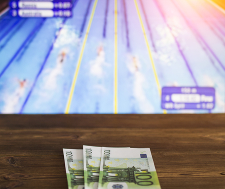 Euro money on the background of the TV on which show swimming, water sports, sports betting, navigation