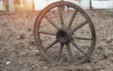 Old wooden wheel from a horse-drawn carriage on arable land, ground, close-up, earth