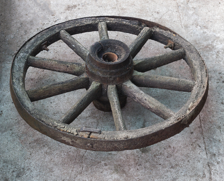 Old wooden wheel from a horse-drawn carriage on a concrete background, close-up, wooden