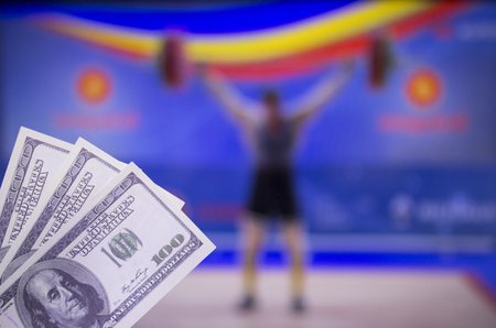 Money dollars on the background of the TV on which show weightlifting, sports betting, Weightlifting
