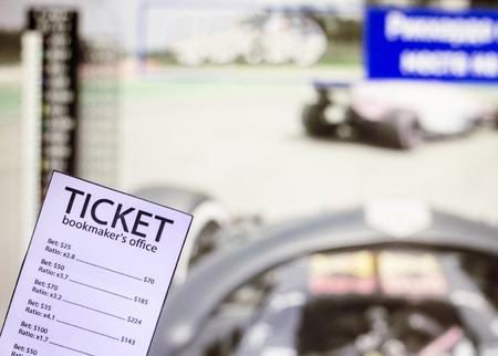 Bookmaker ticket on the background of the TV on which show the sports races the formula, sports betting, betting office