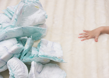 a bunch of baby diapers is lying on a white background, a small child's hand is reaching for them, nappy