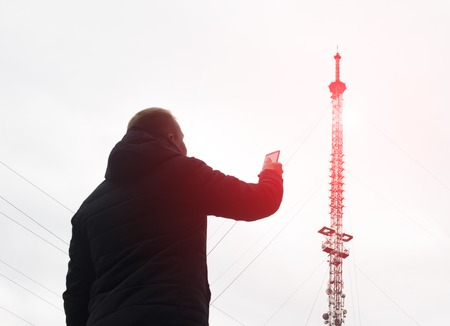 High telecommunication mobile tower from which there is radiation and a man with a mobile phone, poor network, equipment, 4g