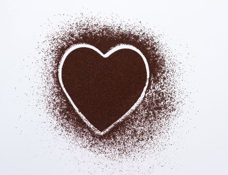 Heart on a white background laid out of ground coffee, close-up, organic