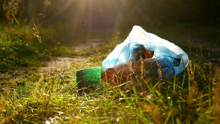 A package of plastic garbage lies in the forest on a forest road, pollution of nature, garbage and nature, the sun, close-up