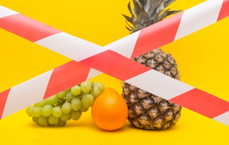 Fruits on a yellow background behind a protective red ribbon, a ban on the importation of fruits and food products, sanctions, prohibition