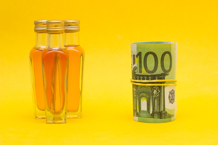 Small bottles with alcohol and euro money, income from the alcohol trade, price increase, close-up, buying alcoho