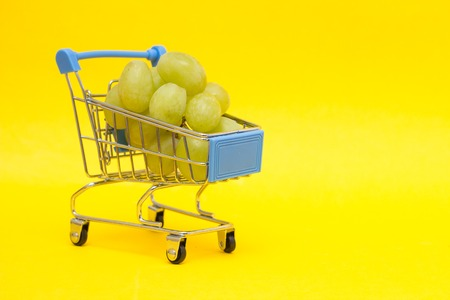 Grapes in a shopping trolley on a yellow background, close-up, copy space Stok Fotoğraf