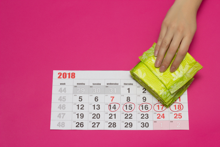 Menstrual women's calendar and a stack of gynecological pads, female hand takes a pad, pink background, copy space, gynecologist, ovulation