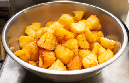 Fried potatoes with a golden crust in a deep fryer, rustic slices