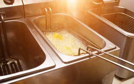 Boiling oil in a deep fryer in which potatoes are country-style, fast-food, sun, junk food, prepared