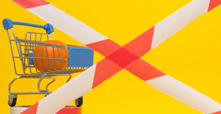 Shopping cart in which lies the mandarin, banned tape, the concept of sanctions on the import of goods and products, background