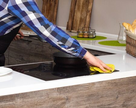 A man doing the cleaning in the modern kitchen, close-up, hand and rag, cleaning Stock fotó