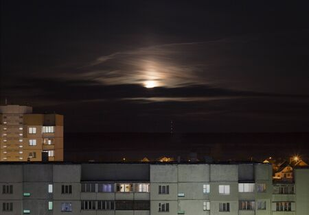 Creepy moon in the night sky against the background of urban houses and buildings, the influence of the moon on humans