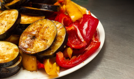 Steamed and roasted vegetables on a barbecue eggplant and red pepper on a plate, close-up, guinea squash