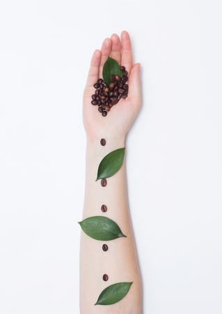 Female hand with coffee grains in the palm and petals on a white background, fashionable handmade art, aroma