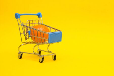 Mandarin in a shopping trolley on a yellow background, close-up, export of food and fruit abroad, political