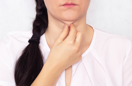 Beautiful girl pulls her hand off a double fat chin, a problem with a hanging chin, white background, close-up