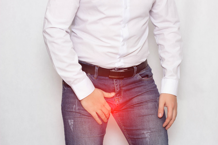 A man on a white background in a white shirt holding on to his groin he has pain and varicocele of the spermatic cord, a problem, varicose veins, spermatogenesis