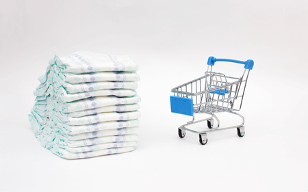 Baby diapers on a white background and a shopping trolley, the concept of buying hygiene products for the child, close-up