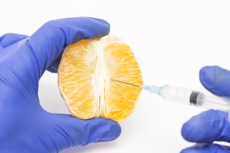 Doctor cosmetologist injects orange into the concept of the labioplasty procedure, reducing or increasing the correction of the labia of the woman s lips Banco de Imagens