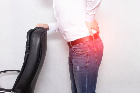 A man holds his back holding an office chair concept of back pain, pinched nerve and myofascial syndrome, inflammation, lumbago