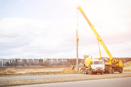 Construction of a new road and installation of lampposts using a truck crane and cement truck, workers, copy space
