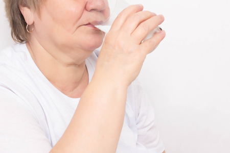 Elderly woman drinks water from a glass on a white background, concept of loss of body fluid in the elderly, dehydration, copy space, urinary system