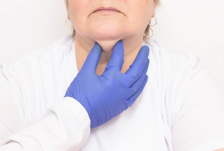 A plastic surgeon examines an aged woman to tighten and get rid of wrinkles and double chins, white background, cosmetologist Reklamní fotografie