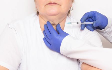 Un médico realiza inyecciones de ozonoterapia y mesoterapia a una mujer en la papada para deshacerse de las arrugas y papada, rejuvenecimiento facial y cutáneo, liposucción