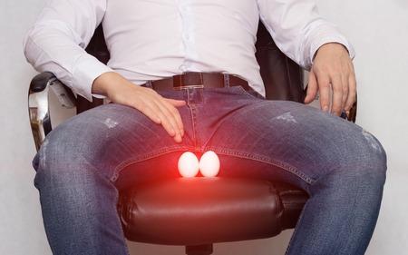 Un uomo in camicia bianca è seduto su una sedia con una cisti dell'epididimo dello scroto, orchite e infiammazione, dolore, spermatocele