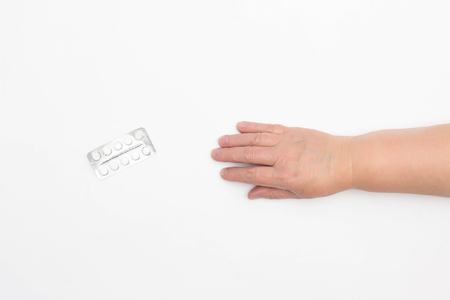 The hand of an elderly woman reaches for pills on a white background, the concept of placebo pills, health, close-up, copy space, myocardium