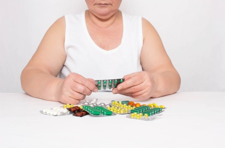 An elderly woman is considering a bunch of pills that lie on the table, the concept of healing and taking synthetic vitamins and pills for heart disease, cardiovascular system, cardiosclerosis Stockfoto