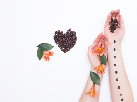 Female hands on a white background with coffee beans and hibiscus flowers, heart of coffee beans, aroma, concept of love and tenderness, cosmetics Banco de Imagens