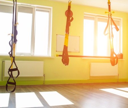 Modern new gym in the fitness center to practice a new sport of the TRX loop, sunset, copy space