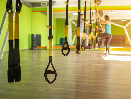 Group lesson with a trainer and training on the sport loop in the new modern fitness complex, copy space, suspension training Stock Photo