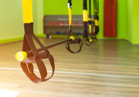 Modern new gym in the fitness center to practice a new sport of the loop, sunset, suspension training, copy space Stock Photo