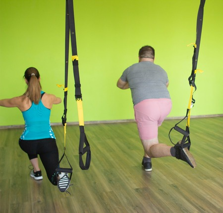 A man and a girl are engaged on the loops of the performing exercises Bulgarian split-squat, strengthening the muscles of the buttocks, legs and quadriceps, drumstick