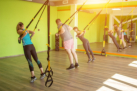 People in the gym are engaged on the loops of the and carry out an exercise of raising hands, to strengthen the muscles, copy space, blurred, calories